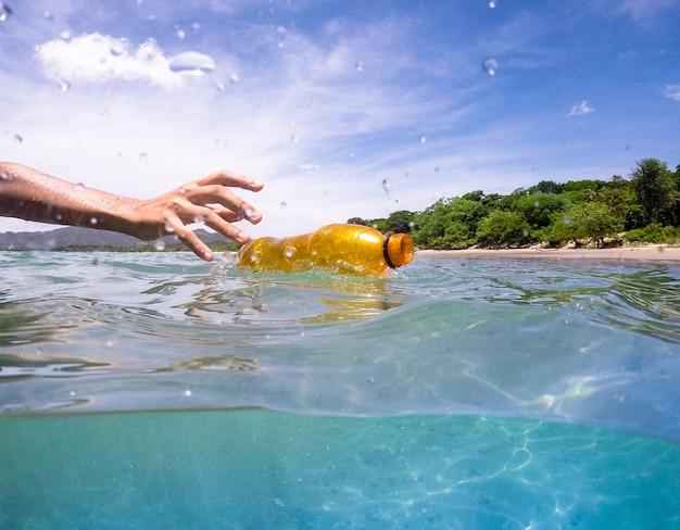 Escolher uma garrafa de plástico do ocwan, reciclar