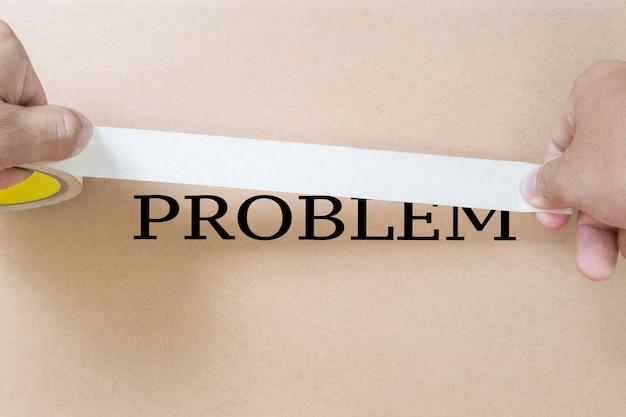 Escondendo o conceito do problema com a mão segurando a fita para encobrir o problema