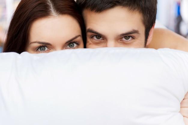 Escondendo o rosto atrás do travesseiro. jovem casal apaixonado, deitado na cama e olhando para fora do travesseiro
