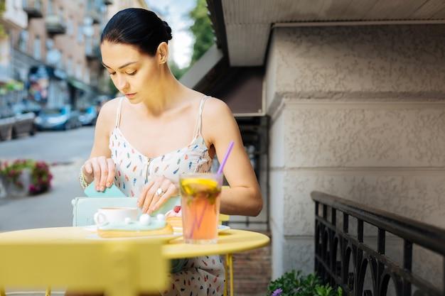 Escondendo um telefone. calma jovem séria visitando um café de rua e parecendo concentrada enquanto esconde seu smartphone em uma bolsa