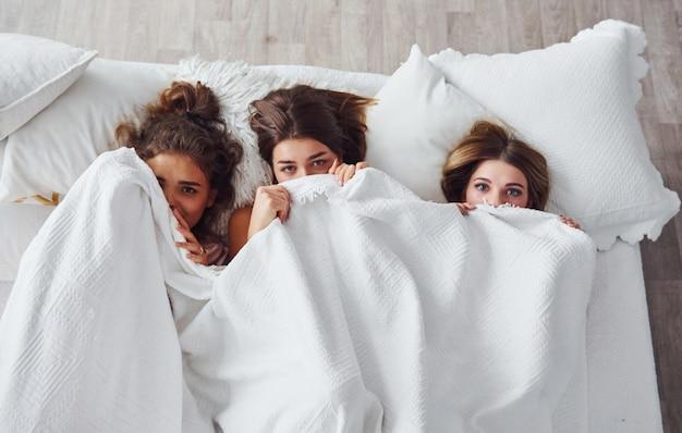 Escondido sob o cobertor. felizes amigas se divertindo na festa do pijama no quarto.