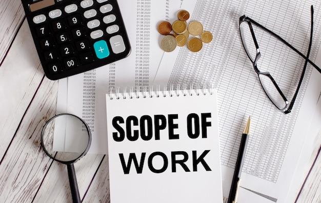 Escopo de trabalho escrito em um bloco de notas branco perto de uma calculadora, dinheiro, óculos, uma lupa e uma caneta