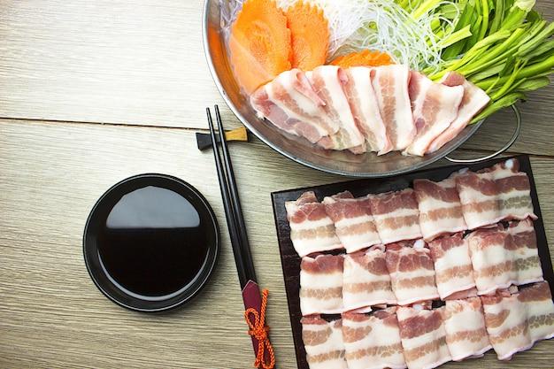 Escorregadio de carne de porco entremeada e legumes em shabu pote em pote de sukiyaki