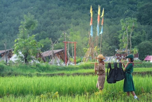 Escoteiros de estudantes asiáticos usando uniformes e máscara