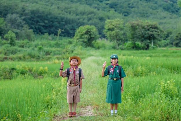 Escoteiros de estudantes asiáticos usando uniformes
