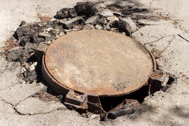 Escotilha de esgoto de metal quebrado no meio de uma estrada de asfalto