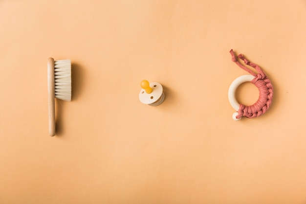 Escova; chupeta e brinquedo em um fundo laranja