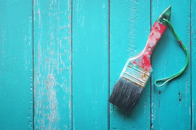 Escova com luz azul tinta sobre fundo de madeira clara pintura de madeira.