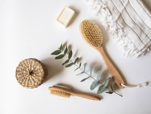 Escova corporal com cabo de madeira, pedra-pomes, caixa de vime, toalha branca e um pedaço de sabão