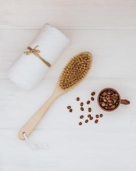Escova corporal de madeira, toalha branca e grãos de café em um fundo branco de madeira.