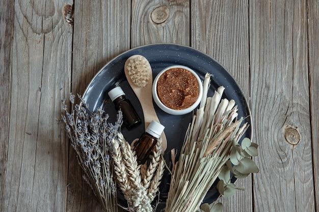 Escova corporal, esfoliante natural, óleos e um buquê de ervas do campo em uma superfície de madeira.