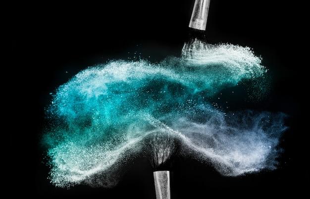 Escova cosmética com pó cosmético azul espalhando