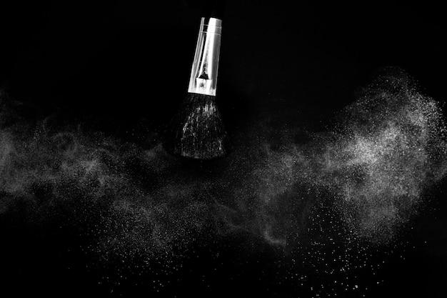 Escova cosmética com pó cosmético branco espalhando para maquiador ou design gráfico em fundo preto