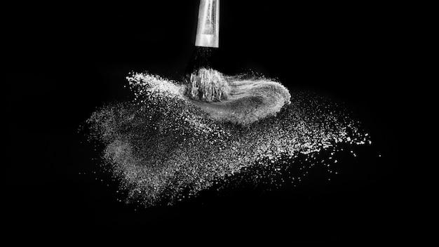 Escova cosmética com pó cosmético branco espalhando