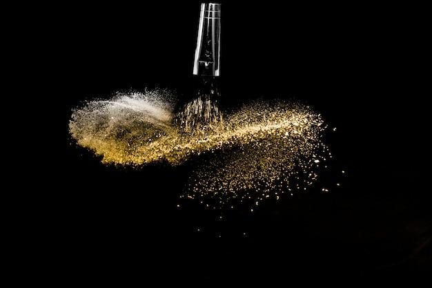 Escova cosmética com pó cosmético dourado espalhando para maquiador e design gráfico em fundo preto