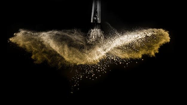 Escova cosmética com pó cosmético dourado espalhando para maquiador