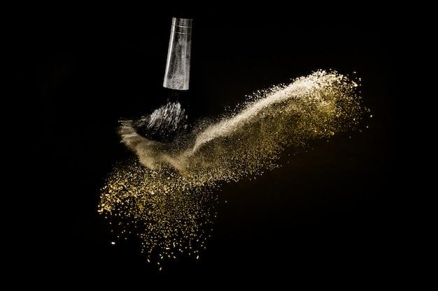 Escova cosmética com pó cosmético dourado espalhando