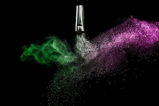 Escova cosmética com pó cosmético verde e rosa, espalhando-se para maquiador e design gráfico em fundo preto