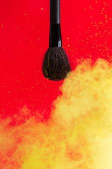 Escova cosmética e nuvem pulverizada de cosméticos em um conceito vermelho