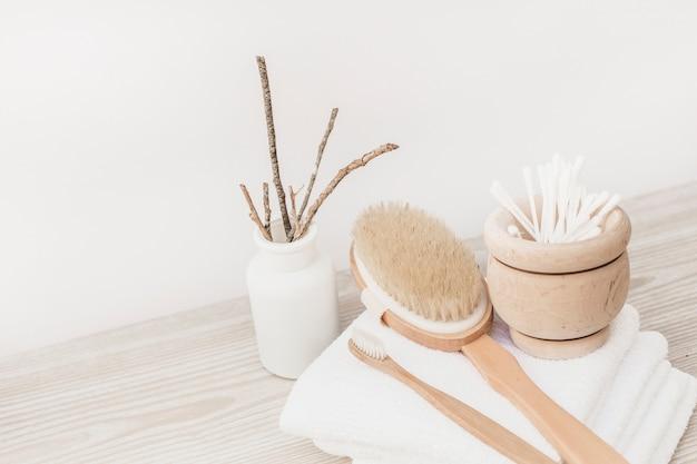 Escova; cotonetes de toalha e algodão na superfície de madeira