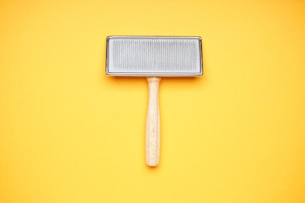 Escova de aliciamento. escova para cães em um fundo amarelo. vista do topo.