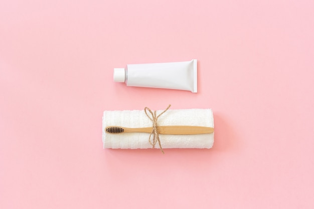Escova de bambu eco-friendly natural na toalha branca e tubo de dentífrico. conjunto para lavar