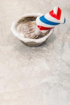 Escova de barba tradicional e tigela com espuma