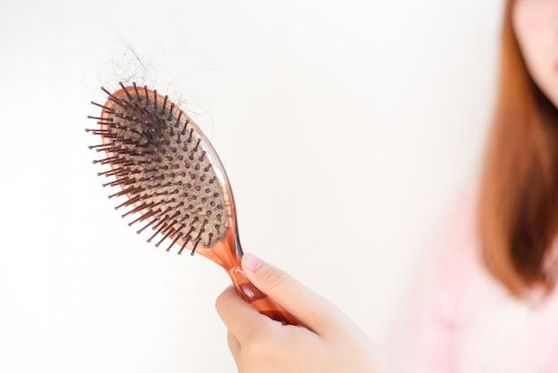 Escova de cabelo da mão das mulheres com perda de cabelo, caspa e problemas de saúde.