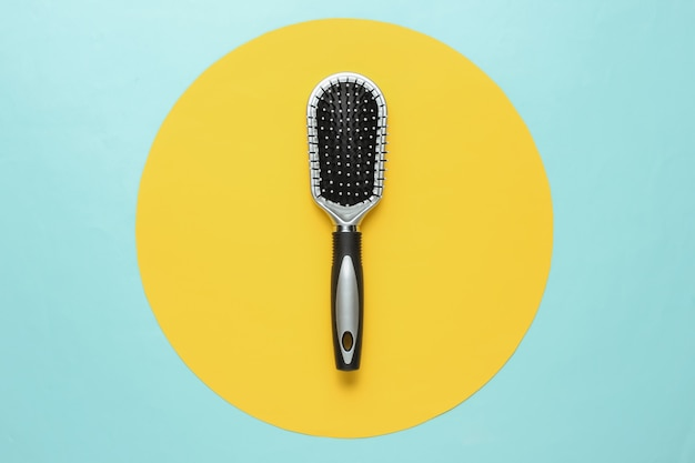 Escova de cabelo elegante em fundo azul com círculo amarelo