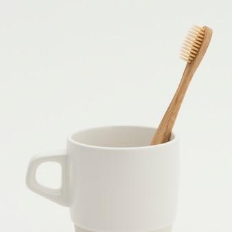 Escova de dente de bambu natural em uma xícara