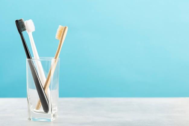 Escova de dente ecológica feita de bambu natural e duas escovas de dente de plástico em um copo de vidro sobre uma mesa de madeira, fundo azul