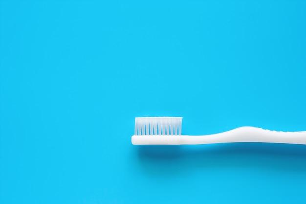 Escova de dentes branca usada para limpar os dentes no fundo azul