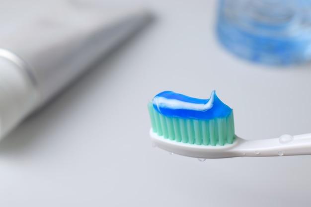 Escova de dentes com gota de água e creme dental no fundo desfocado