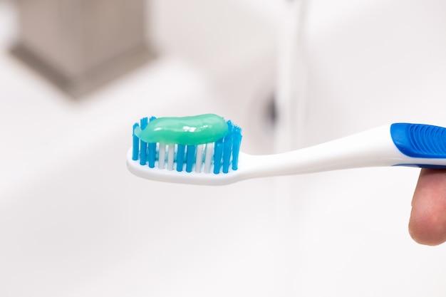Escova de dentes com pasta de dente na mão do cara no lavatório.