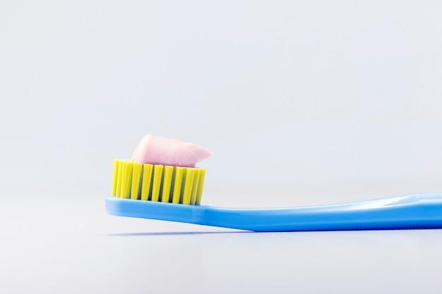 Escova de dentes com pasta de dentes em fundo cinza com espaço de cópia. conceito odontológico.