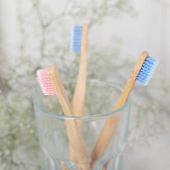 Escova de dentes de bambu cor-de-rosa e azul em uma taça de vidro ninguém, formato quadrado. responsabilidade socioambiental. conceito amigável de eco