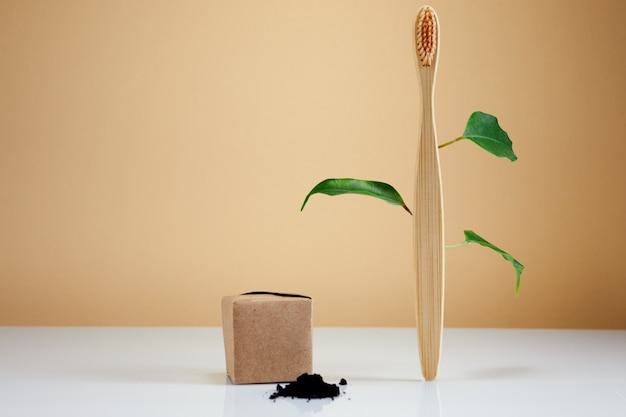 Escova de dentes de bambu de madeira com folhas e pasta de dentes de carvão preto como conceito criativo ecológico. produto de beleza orgânico natural do banheiro.