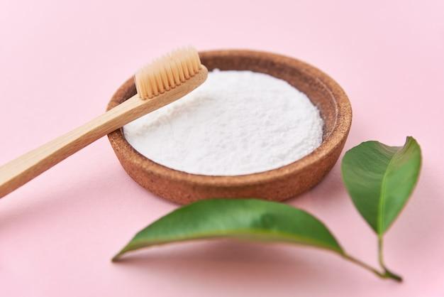 Escova de dentes de bambu de madeira e bicarbonato de sódio em uma rosa.
