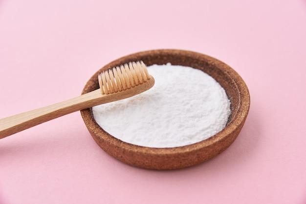 Escova de dentes de bambu e bicarbonato de sódio em um fundo rosa. conceito de desperdício zero