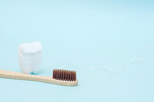 Escova de dentes de bambu e fio dental branco na forma de um dente branco sobre fundo azul.