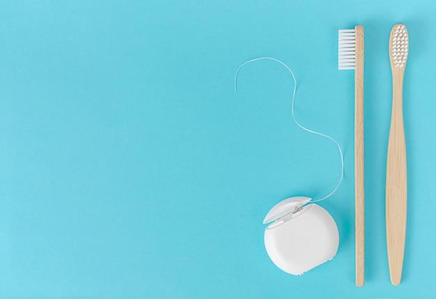 Escova de dentes de bambu e fio dental sobre fundo azul.