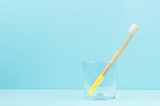 Escova de dentes de bambu ecológica em um vidro transparente sobre um fundo azul com espaço de cópia. zero conceito de desperdício.