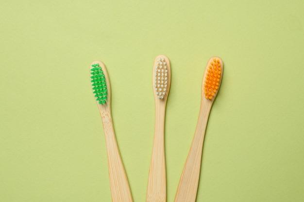 Escova de dentes de bambu em um fundo verde. vista do topo.