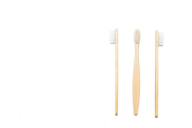 Escova de dentes de bambu em uma parede isolada, artigo de limpeza de dentes sobre como escolher