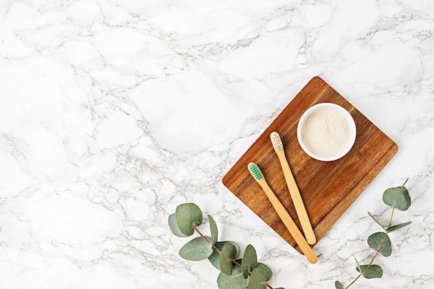 Escova de dentes de bambu sem plástico e pó dental natural. conceito de higiene pessoal sustentável, ecologicamente correto e zero resíduos. vista superior, configuração plana