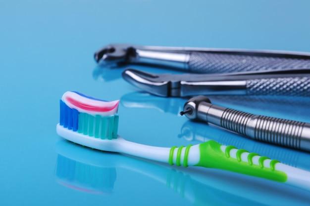 Escova de dentes de cuidados dentários com ferramentas de dentista no fundo do espelho