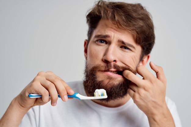 Escova de dentes de homem na higiene das mãos limpar os dentes de fundo claro
