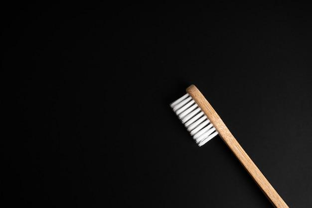 Escova de dentes de madeira de bambu antibacteriana ecológica com cerdas brancas em um fundo preto. cuidar do meio ambiente é tendência. copie o espaço.