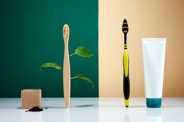 Escova de dentes de madeira em bambu com folhas vs escova de plástico. produto de beleza orgânico natural do banheiro. vida sem plástico.