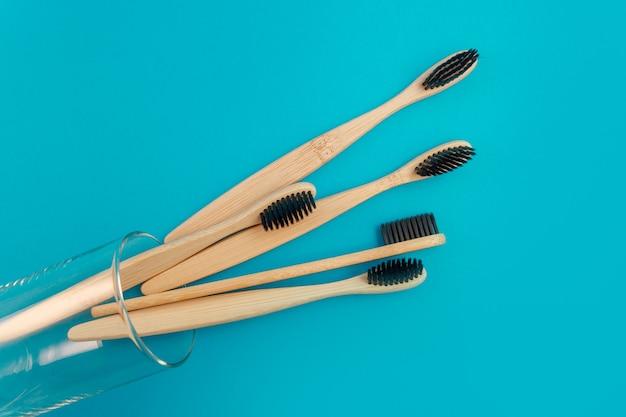 Escova de dentes de madeira em um fundo azul em um copo